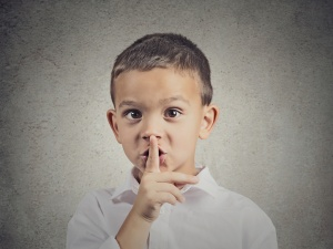 Closeup portrait young serious child, boy placing finger on lips as if to say, shhh, be quiet, silence, isolated grey wall background. Facial expression, human emotions, signs, symbols, body language