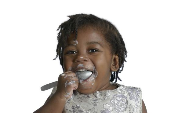 Afrikanisches Baby bekleckert sich beim Essen