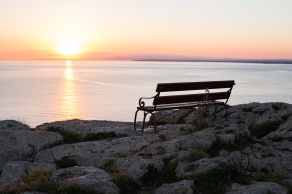Sunset beach and bench. Bench by the sea in the sunrise