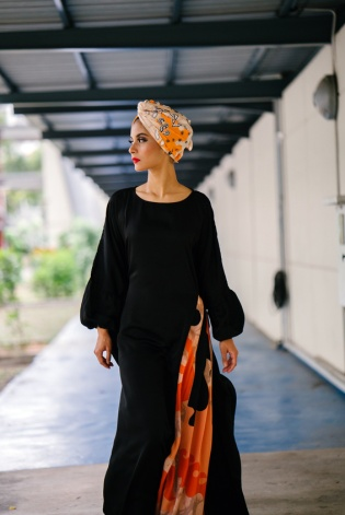 A stylish and fashionable Muslim Malay woman walks down a corridor during the day. She is wearing a colorful turban and a flowing and comfortable ethic garment.