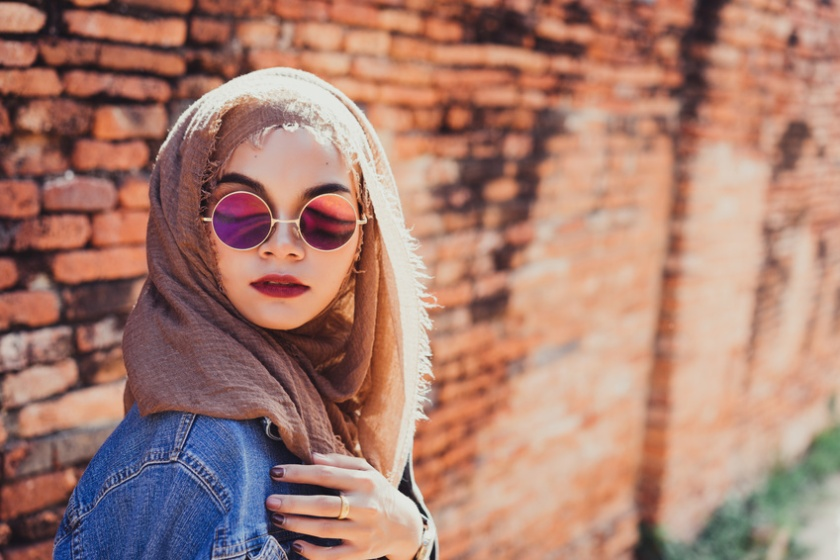 Fashion portrait of young beautiful muslim woman and old brick wall background with copy spaces.